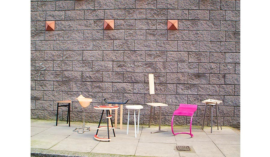Display of chairs against a street wall