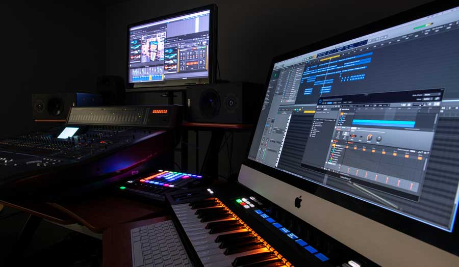 equipment in a music surround sound studio, 2 screens, keyboards and mixing decks