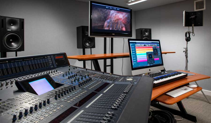 a large mixing deck at the front of the photo, 2 screens and 2 keyboards further away and 3 large speakers in the background