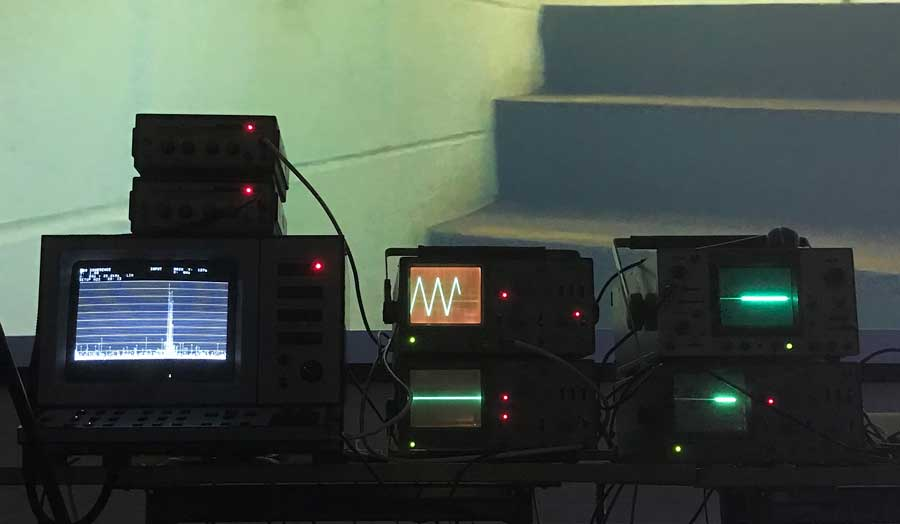 3 pieces of sound recording equipment, all with screens of different sizes with different images on them, places at the bottom of concrete stairs
