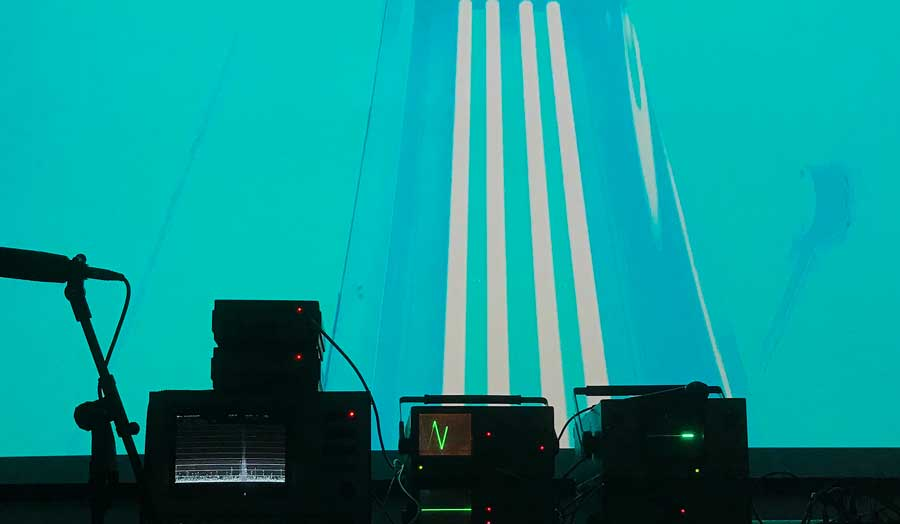 3 pieces of equipment and a standing microphone in the dark in the forefront, in front of them a wall lit up in blue with white stripes in the middle