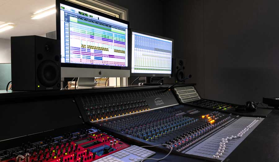 a mixing deck and 2 screens in a music control room