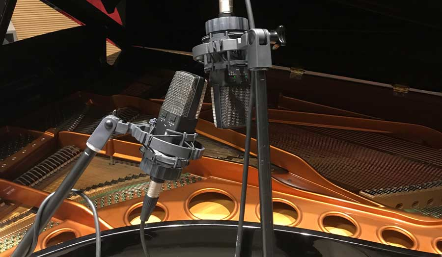 a close up of an open and lit up Bosendorfer grand piano with 2 microphones near it for recording