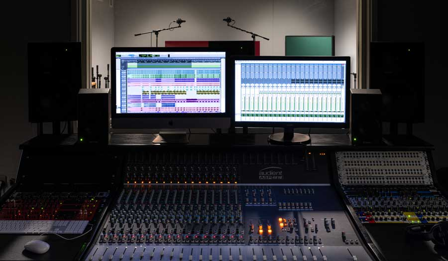 a mixing deck and 2 screens in a music control room, a live recording room behind them