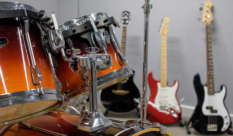 a drum kit in the forefront and 3 guitars in the background leaning against a wall