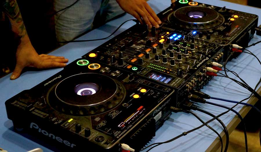 Hands on the dials of a dj mixing deck