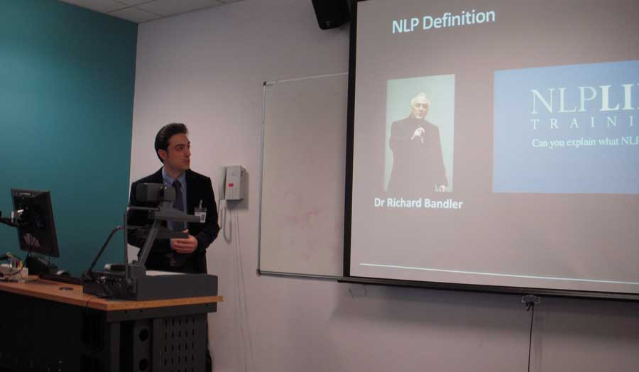 London Met University academic presenting in front of a screen with an image of Dr Richard Bandler