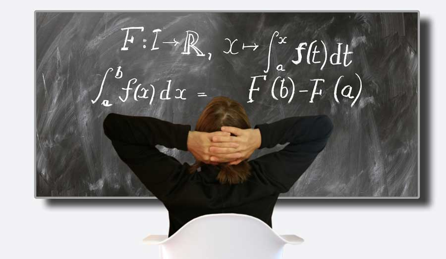a person sitting in a white chair facing a blackboard with mathematical calculus on it