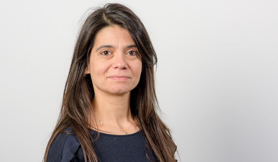 Long-haired female academic Dr Eirini Meimaridou smiles to the camera.