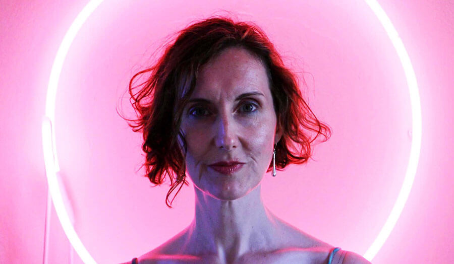 Suzanne Cohen stands against a pink background