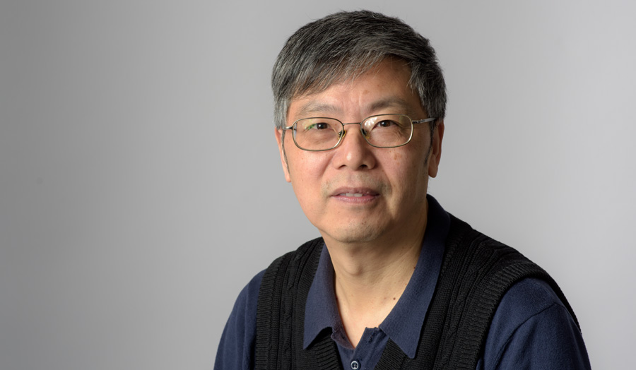 Bespectacled male lecturer Tingkai Wang looks to camera as he poses against a grey background.