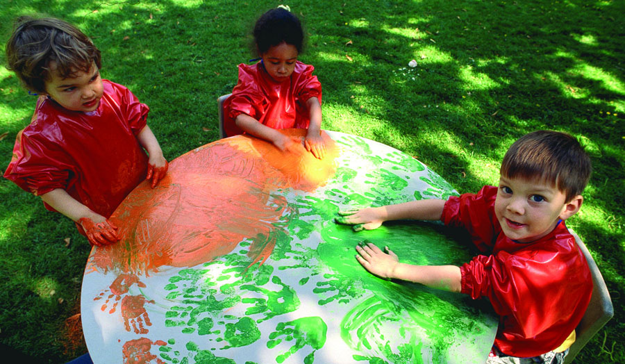 photo of children painting with hands