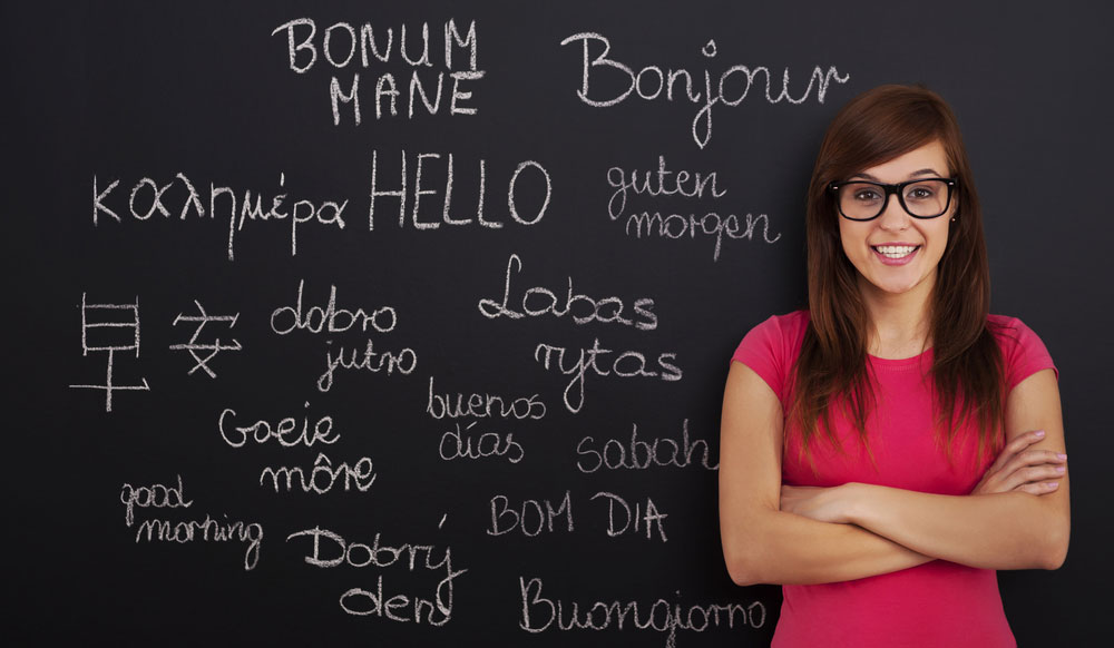 A woman standing in front of a blackboard with different languages on it