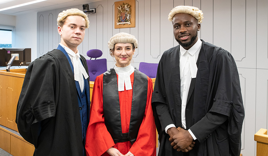 Three people wearing formal court dress including gowns and wigs