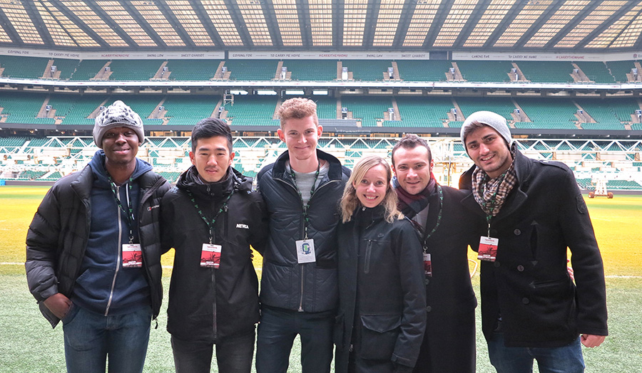 London Met students stand at the edge of the famous Twickenham turf, with the east stand in the back