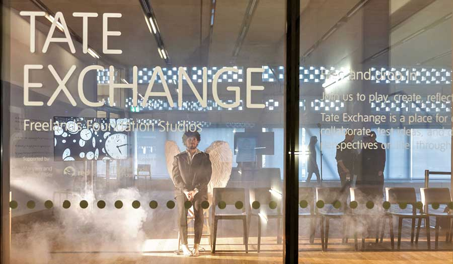 A performance artist dressed as an angel seen through the window of the Tate Exchange exhibition