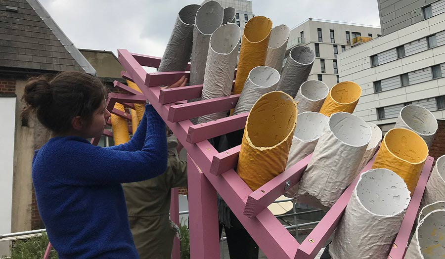 A sculpture on the rooftop of a building made of cardboard painting tubes going through a pink wooden structure