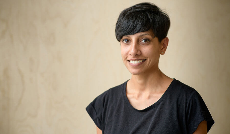 Alpa Depani, a female lecturer with short hair in a black T-shirt, smiles to camera.