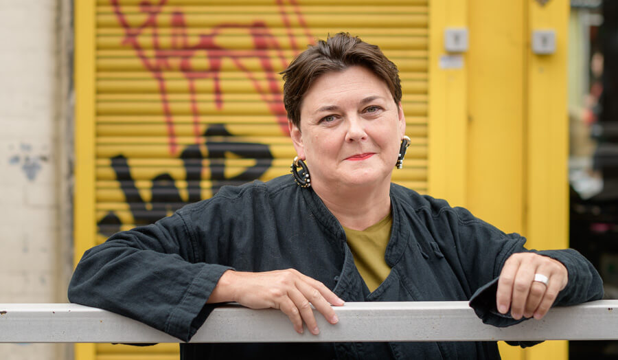 Short haired female lecturer Harriet McKay smiles to the camera as she stands against some graffiti.