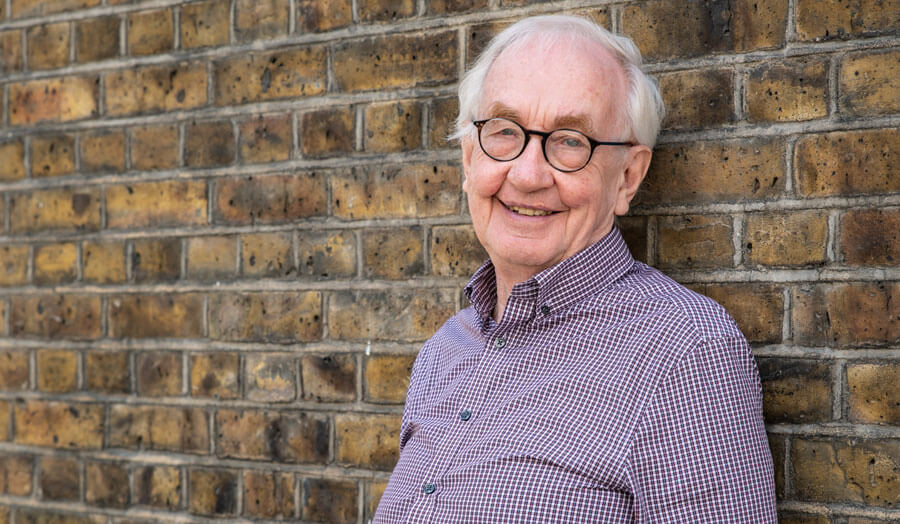Professor Fergus Nicol leaning against a brick wall and smiling to camera