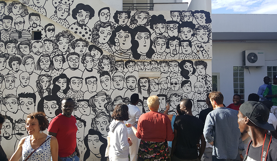 Young people and wall of illustrated faces