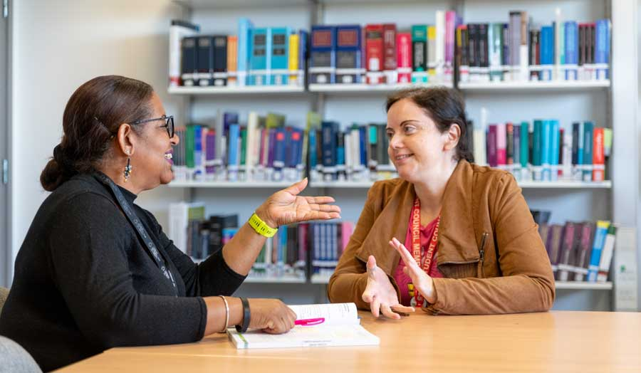 Antonella Petrocco chatting to a librarian in the library