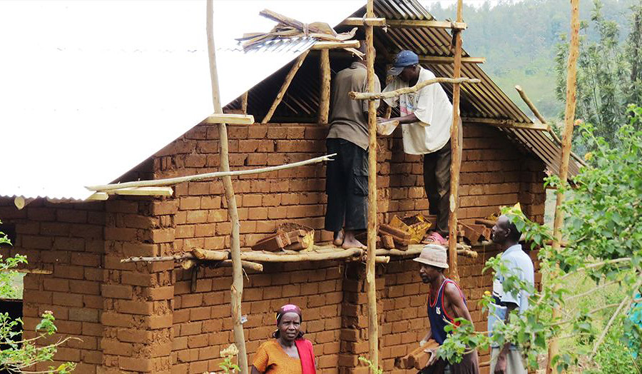 Cooperative members climb the timber pole scaffold to lay the last row of CEBs