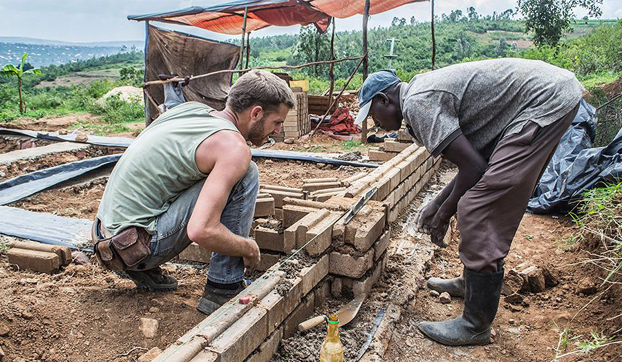 Edward Dale-Harris on site laying blocks with Fabienz Uwiragiye
