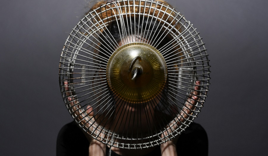 Image of electric fan held in front of woman's face.