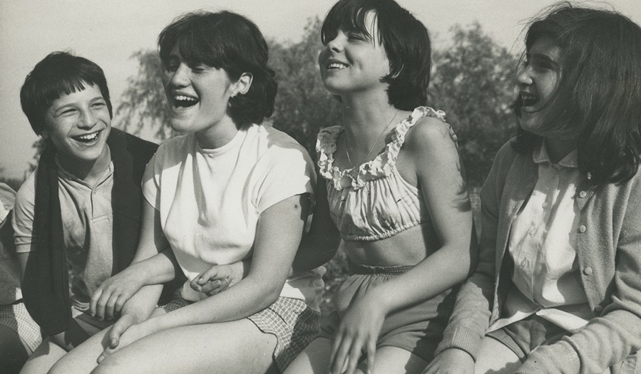 black and white image of four  girls on a wall