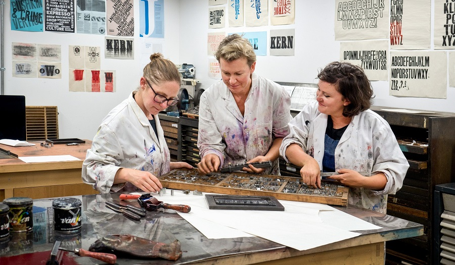 three women look at letterpress