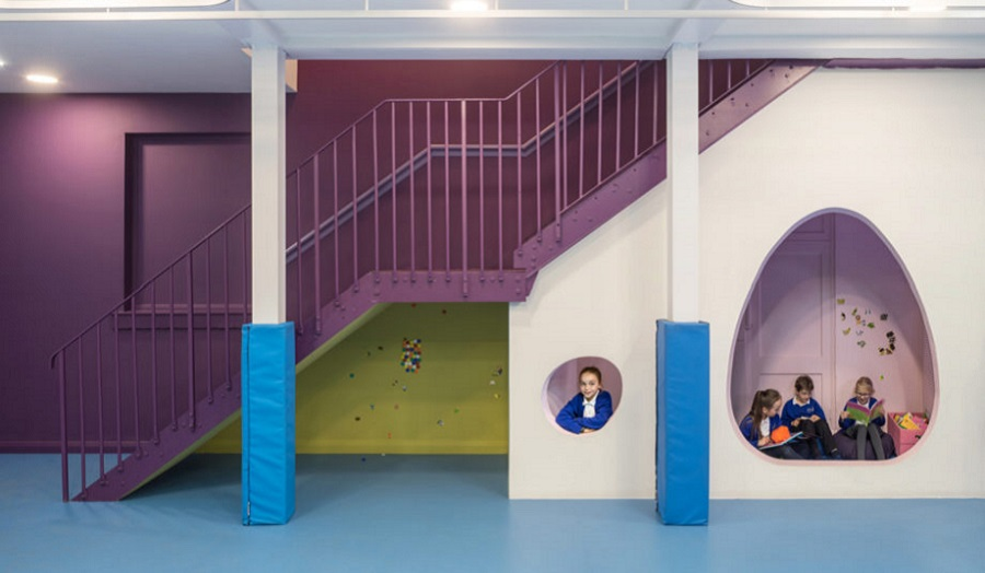 children play in spaces under a staircase
