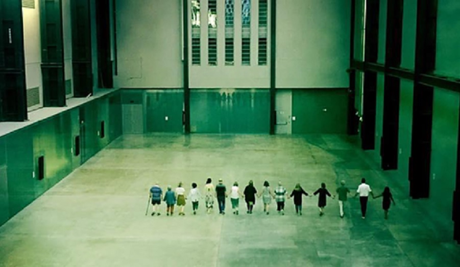 a line of people walk in tate turbine hall