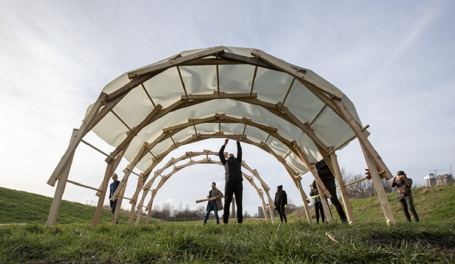 group of people under a large wooden arch in a field