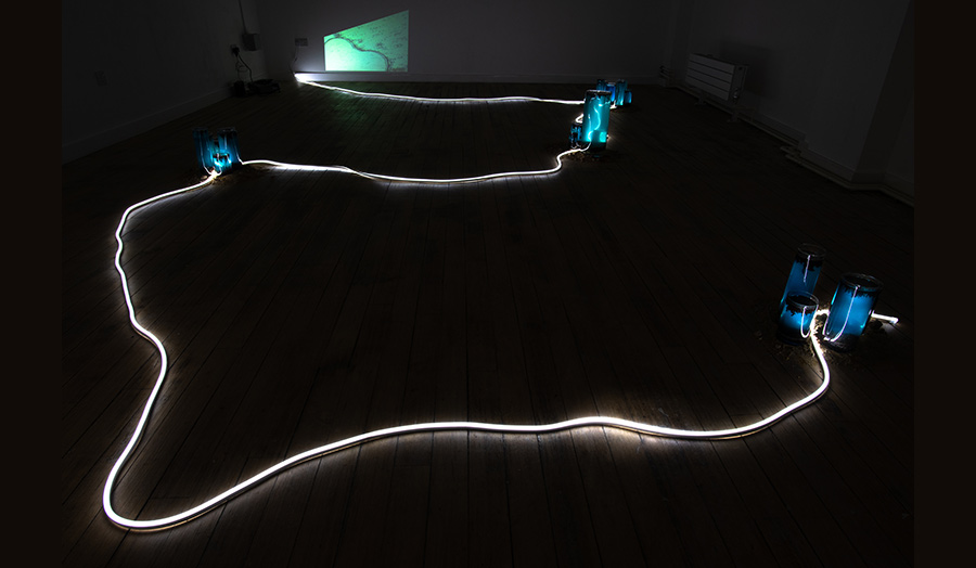 A neon light tube swirling on a dark room's wooden floor