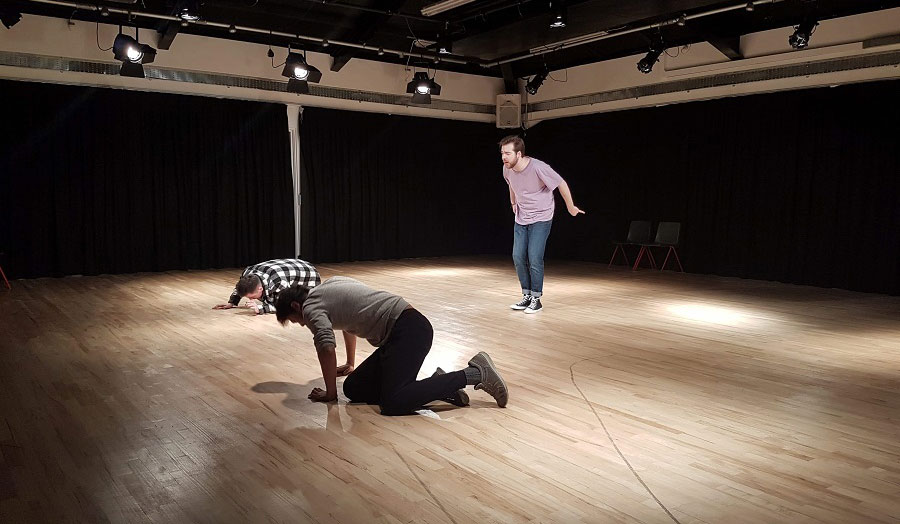 Two men kneeling down on a wooden floor while another man is standing