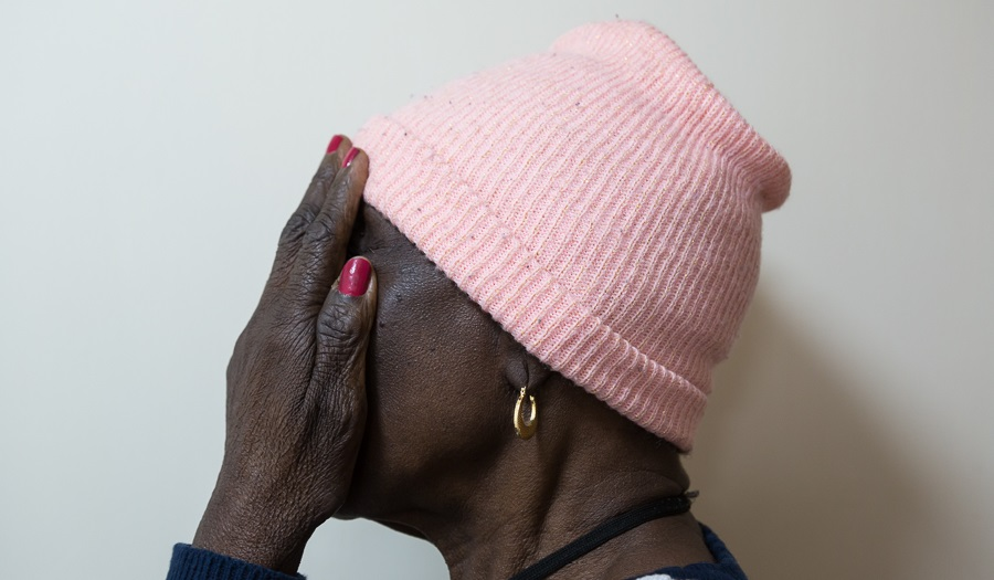 a woman in a pink hat seen from side with gold earring holds hands over face