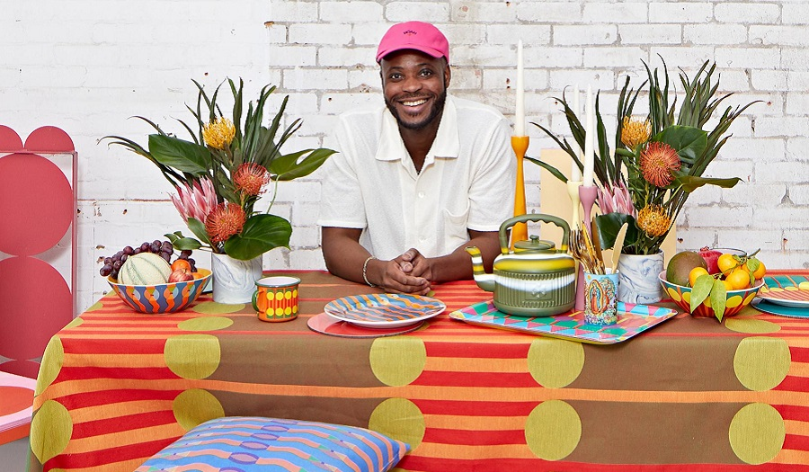 A man sits at a table covered in colourful homeware design products