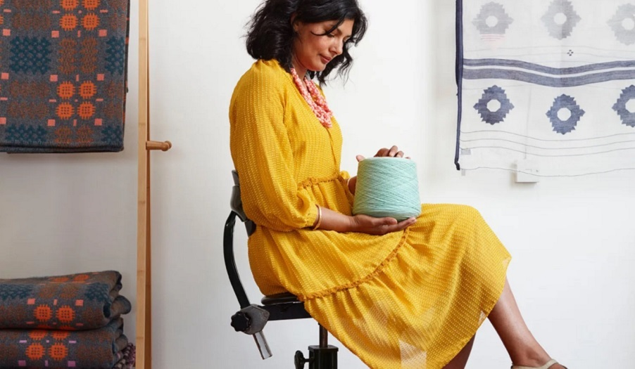 woman in yellow dress sits holding roll of yarn