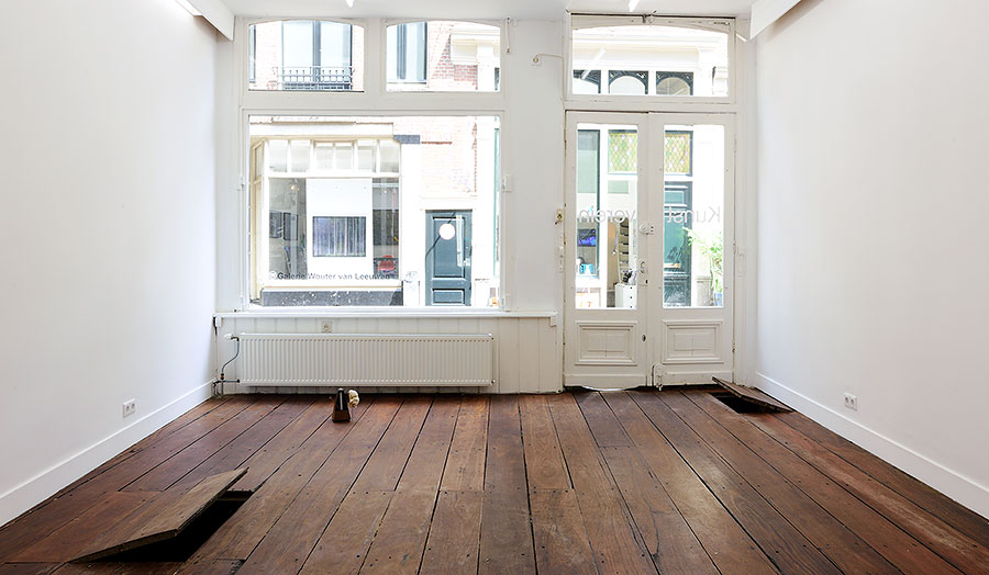 View from inside of an empty white room with a wooden floor over looking to the high street
