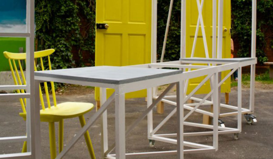 A set of folding tables and door-frames with yellow doors fitted in.