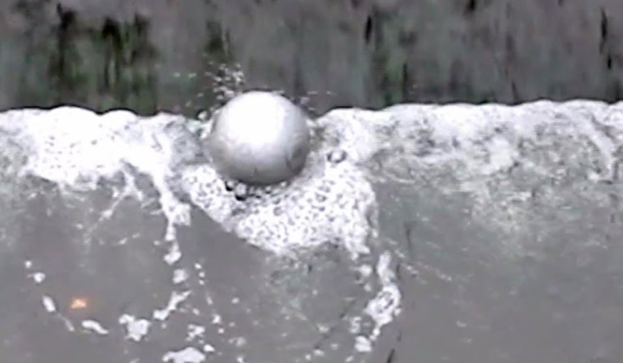 Photograph of a ball in water, part of the artwork by Oliver Hickmet.