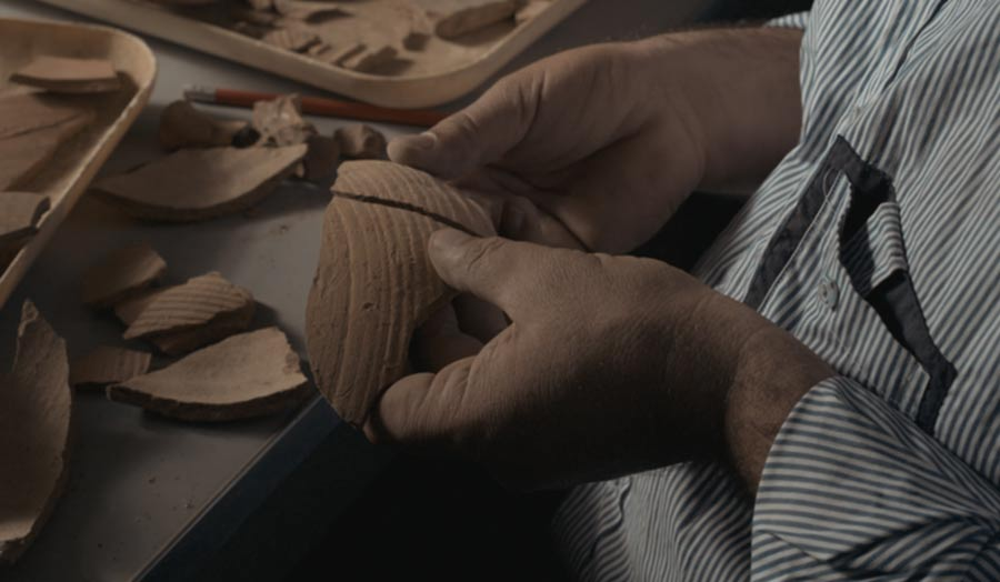 Hands holding pieces of terracotta fragments