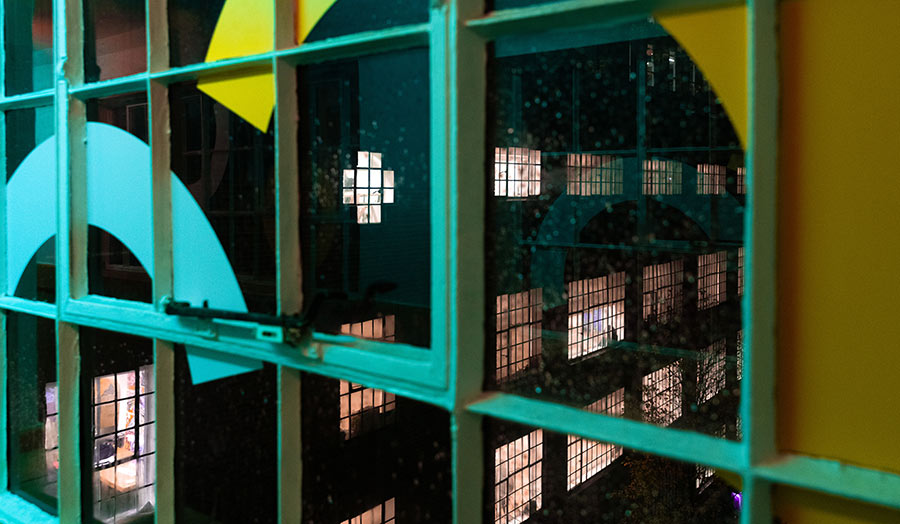 The view of the annex building at night through a window on the bridge over the street that connects the two buildings