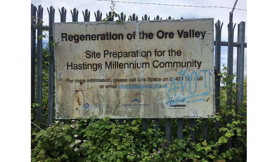 A metal fence with a sign that reads, Regeneration of the Ore Valley