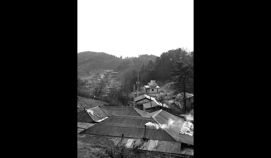 A black and white photograph showing the rooftops of a village in a valley