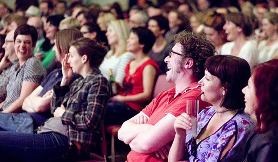 A seated audience laughing