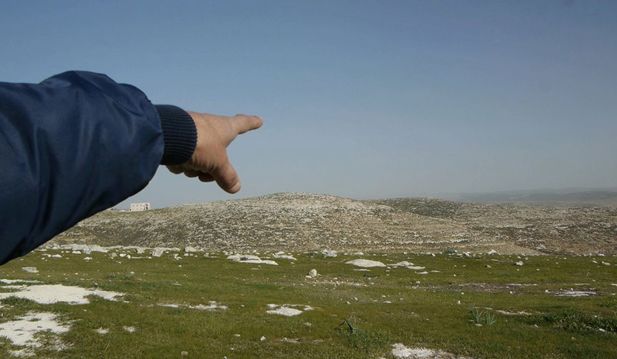 An extended arm and finger pointing to the horizon in an rural landscape