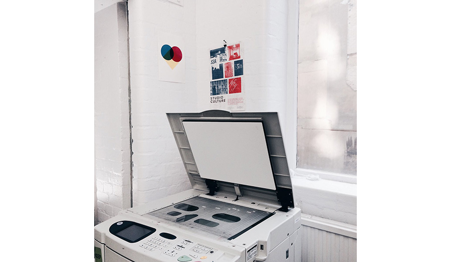 A digital printing machine in a corner of a room with its lid left open