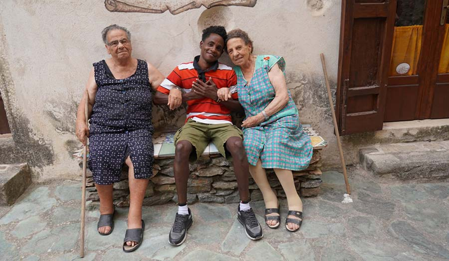 A refugee young man sitting on a bench and being embraced by two elderly women